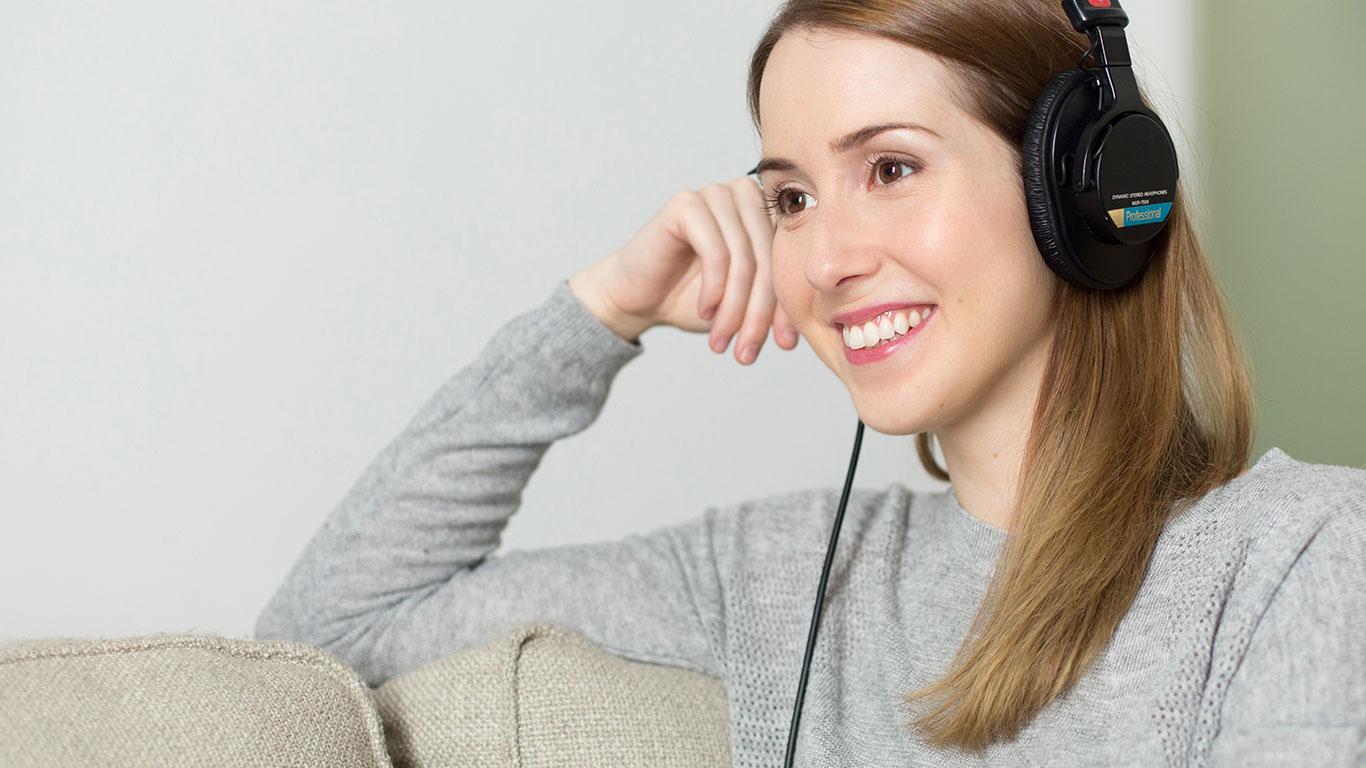Junge Frau lächelt mit Kopfhörer
