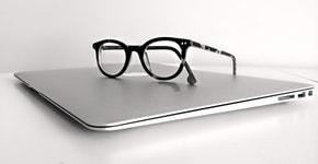 dunkle Brille auf silbernem Laptop
