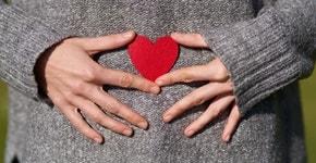 Selbstliebe Herz auf den Bauch haltend